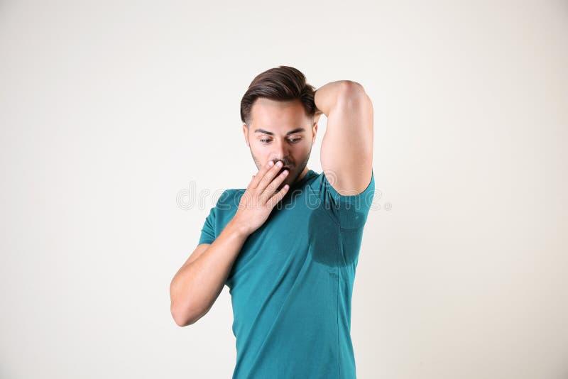 Verschwitzter Mann mit Fleck auf T-Shirt gegen weißen Hintergrund lizenzfreie stockbilder