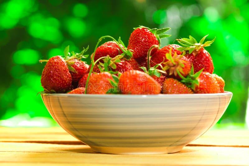 Verse aardbeien in een blauwe plaat op vage achtergrond stock afbeeldingen