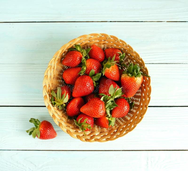 Verse aardbeien in een mand op een blauwe houten hoogste mening als achtergrond stock foto