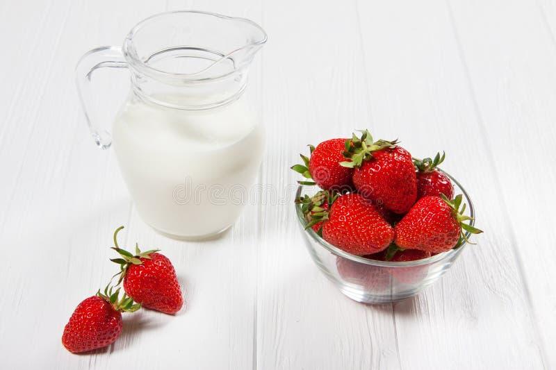 Verse aardbeien en melkkruik op witte houten lijst stock foto
