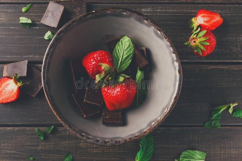 Verse aardbeien met chocolade in rustieke kom stock foto's