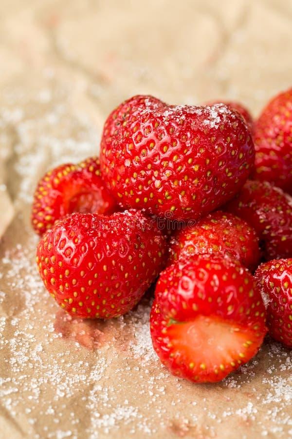 Verse aardbeien met suiker op het gerimpelde bruine pakdocument stock afbeeldingen