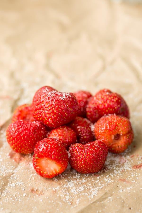 Verse aardbeien met suiker op het gerimpelde bruine pakdocument royalty-vrije stock afbeeldingen