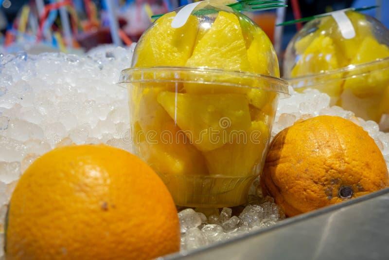 Verse ananasstukken in plastic transparante koppen en sinaasappelen op ijs voor verkoop bij landbouwersmarkt stock fotografie