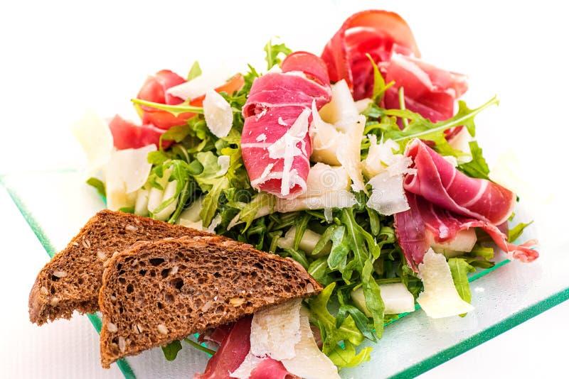 Verse arugula plantaardige salade met ham, kaas en broodplakken op glasplaat op witte achtergrond, productfotografie F royalty-vrije stock afbeeldingen