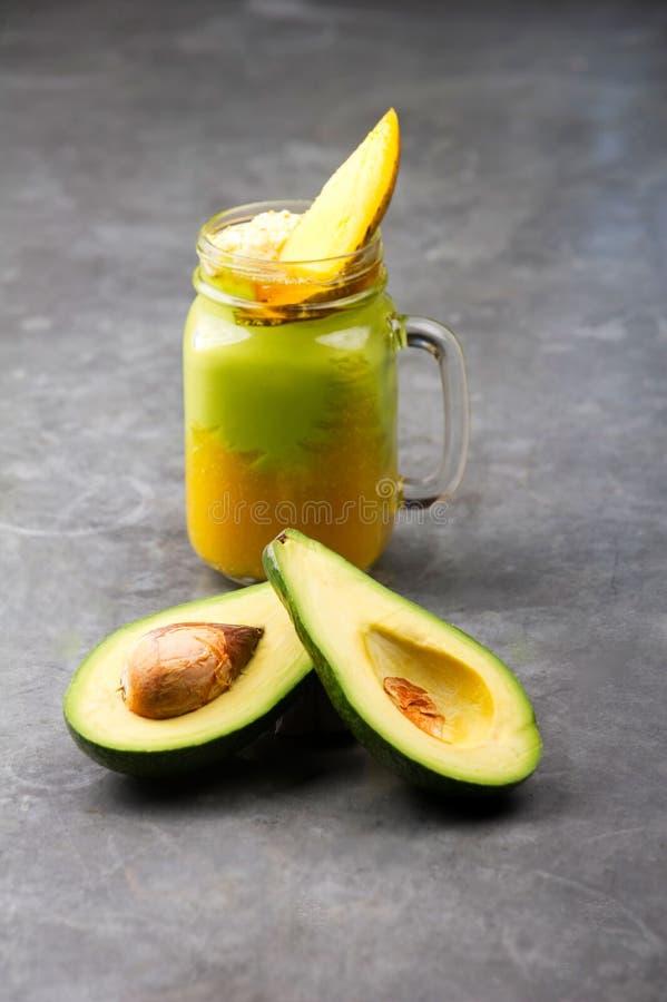 Verse avocado en mango smoothie op een grijze uitstekende lijst royalty-vrije stock afbeelding