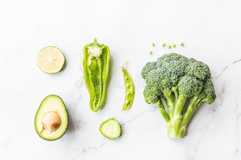 Verse avocado, kalk, broccoli, groene erwten, komkommer, groene paprika Vlak leg Het concept van het voedsel Groene groenten die  stock afbeeldingen