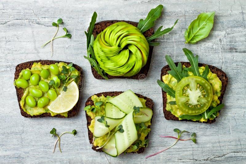 Verse avocadotoosts met verschillende bovenste laagjes Gezond vegetarisch ontbijt met rogge wholegrain sandwiches stock afbeelding