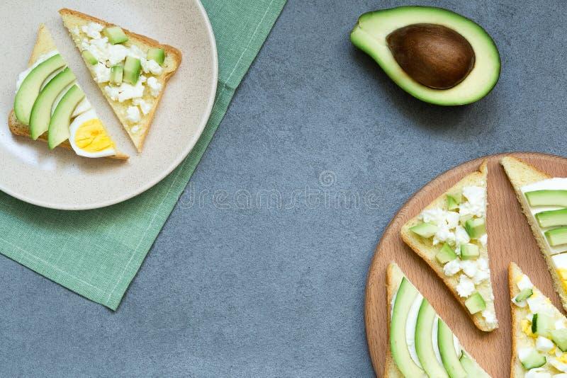 Verse avocadotoosts met verschillende bovenste laagjes Gezond vegetarisch ontbijt met rogge wholegrain sandwiches, hoogste mening stock afbeeldingen
