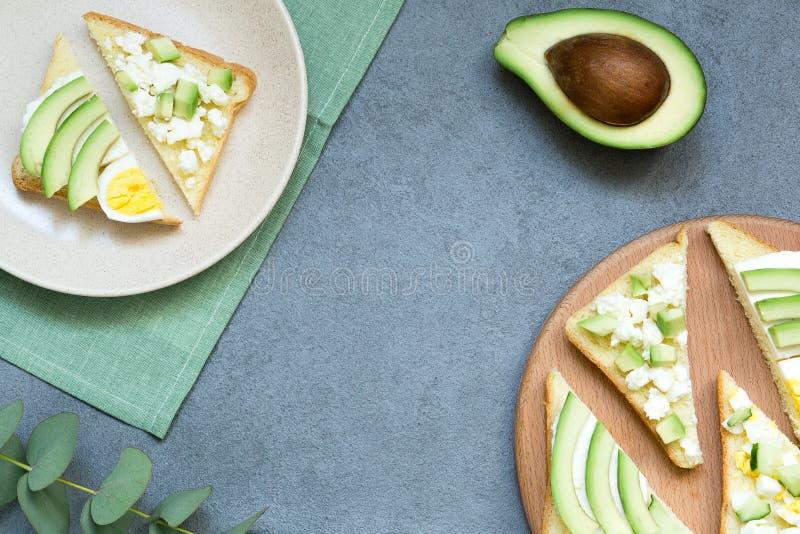 Verse avocadotoosts met verschillende bovenste laagjes Gezond vegetarisch ontbijt met rogge wholegrain sandwiches, hoogste mening stock foto