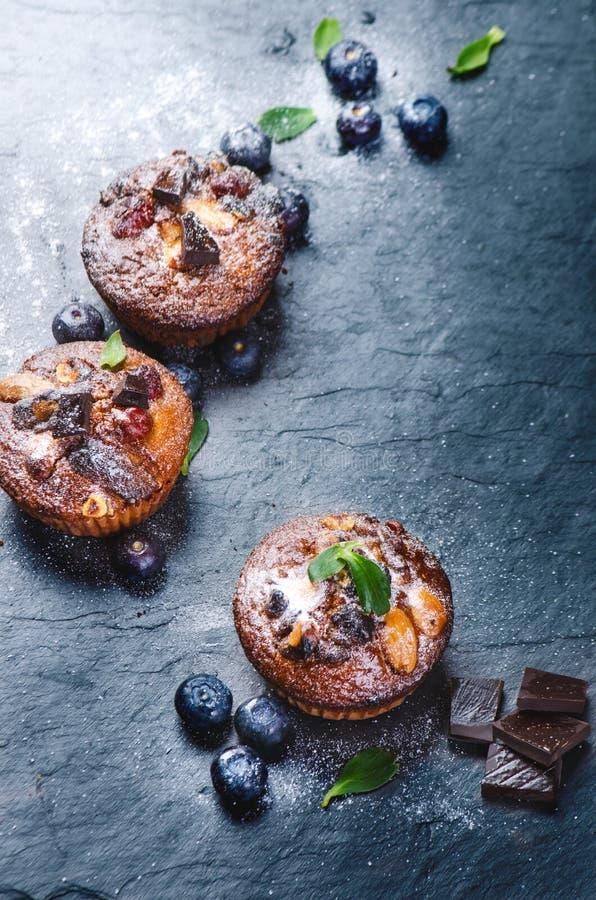 Verse, bosbessenmuffins op een steenachtergrond met suiker en vruchten De achtergrond van het voedsel Concept gebakje stock fotografie