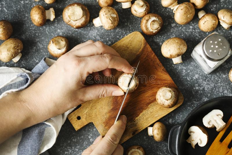 Verse bruine champignonpaddestoelen Sluit de handen van de vrouw omhoog snijden verse paddestoelen stock afbeelding