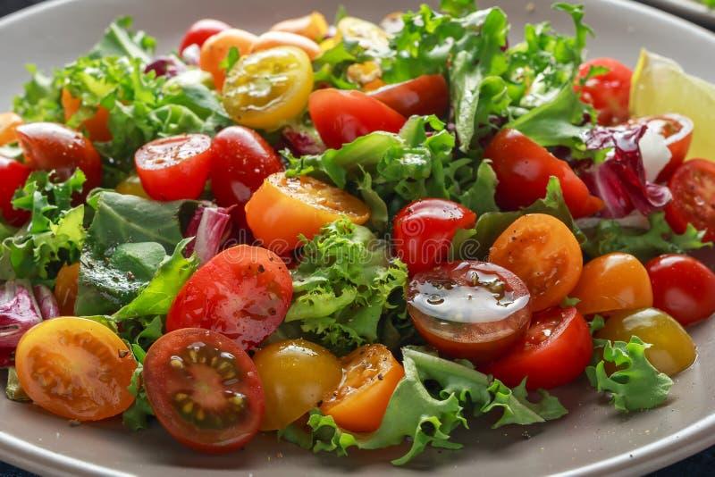 Verse Cherry Tomato-mengelingssalade met sla, citroen, kalk, zwarte peper en overzees zout Gezond voedsel stock fotografie