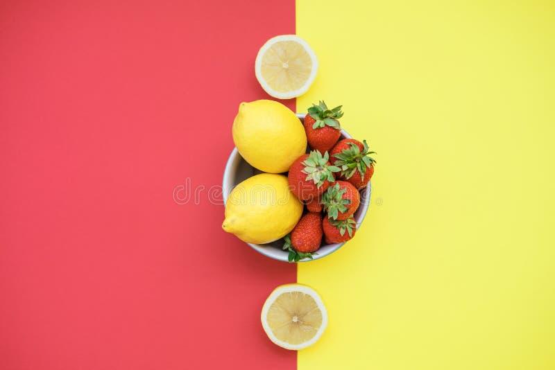 Verse citroenen en aardbeien in een kom op een gele en rode rug stock afbeelding