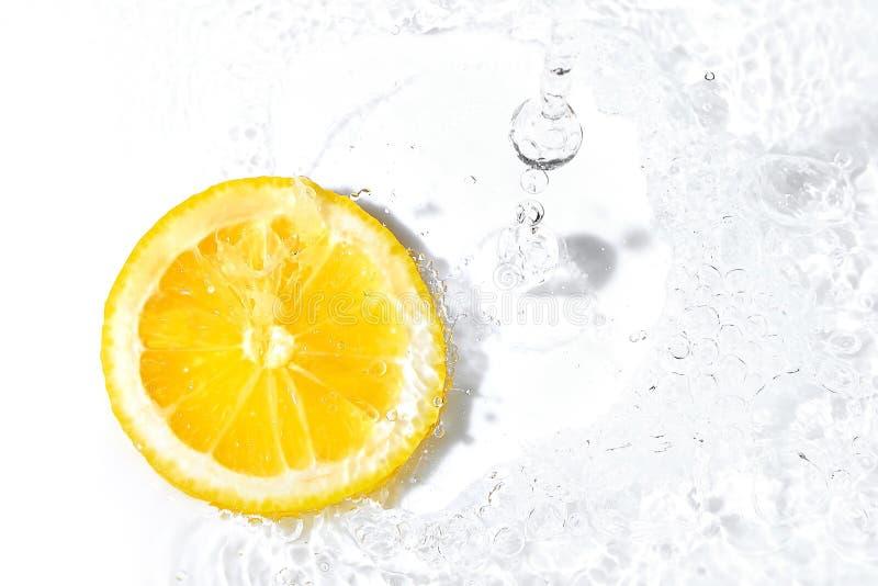 Verse citroenplak en waterplons stock foto's