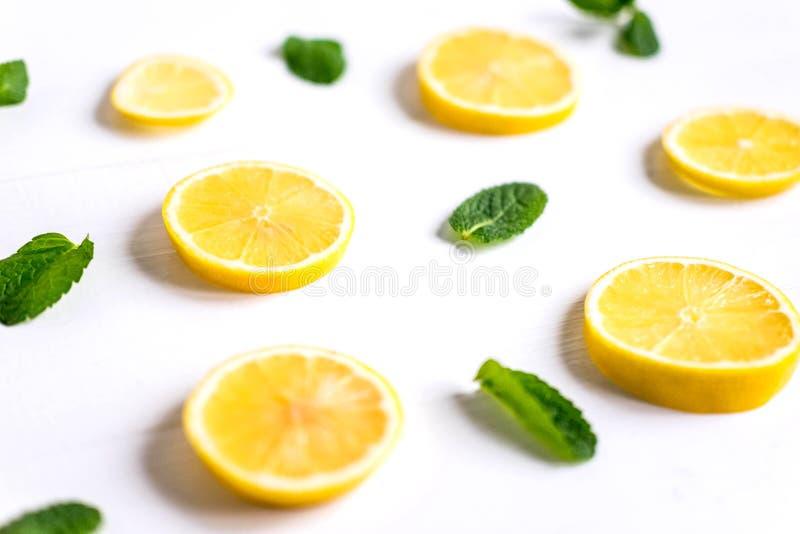 Verse citroenplakken op een witte achtergrond Achtergrond met citroen en munt Mooie foto met citrusvrucht Vitamine C Citroen stock afbeelding