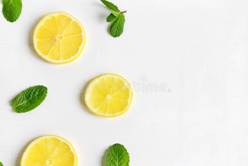 Verse citroenplakken op een witte achtergrond Achtergrond met citroen en munt Mooie foto met citrusvrucht Vitamine C Citroen en V royalty-vrije stock foto
