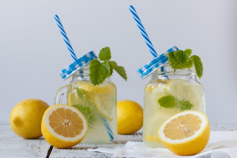 Verse citrusvruchtenlimonade met kalk en citroenen in metselaarkruiken royalty-vrije stock foto