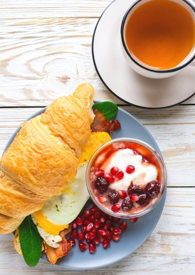 Verse croissantsandwich, eigengemaakte yoghurt, granaatappel en thee stock fotografie
