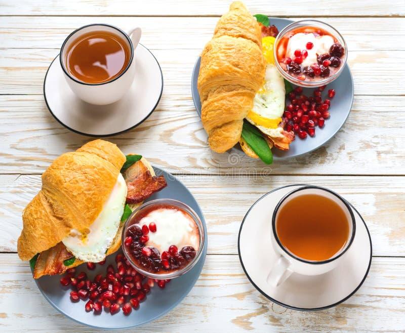 Verse croissantsandwich, eigengemaakte yoghurt, granaatappel en thee royalty-vrije stock afbeeldingen