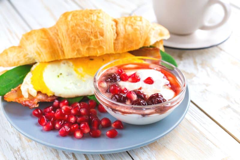 Verse croissantsandwich, eigengemaakte yoghurt, granaatappel en thee royalty-vrije stock foto