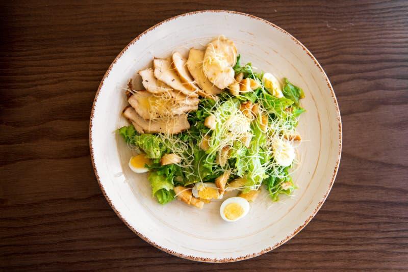 Verse de zomersalade Caesar met eieren, sla, kippen en parmezaanse kaaskaas op witte plaat op houten achtergrond; gezond concept stock foto's