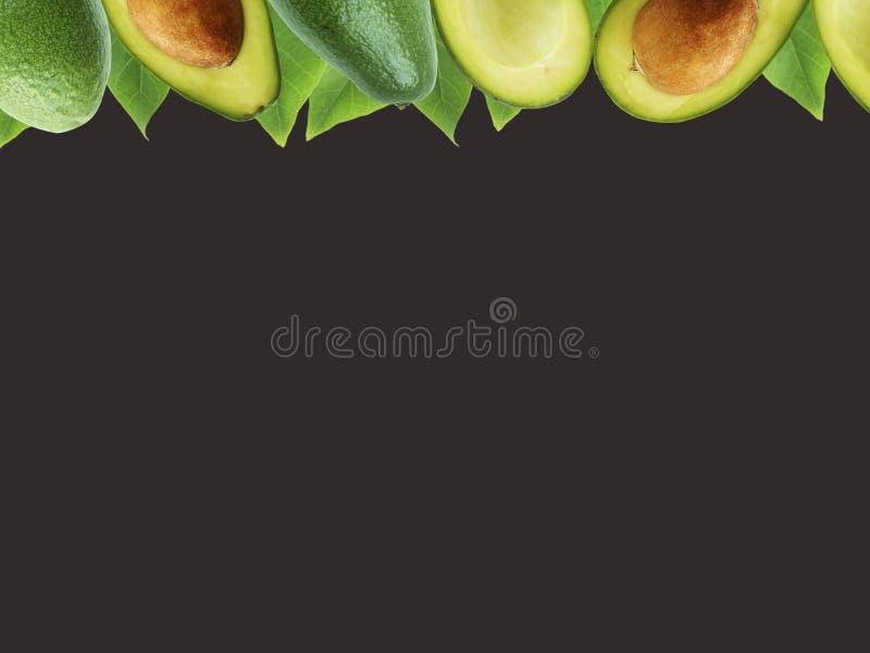 Verse die avocado met bladeren op zwarte achtergrond worden geïsoleerd royalty-vrije stock afbeelding