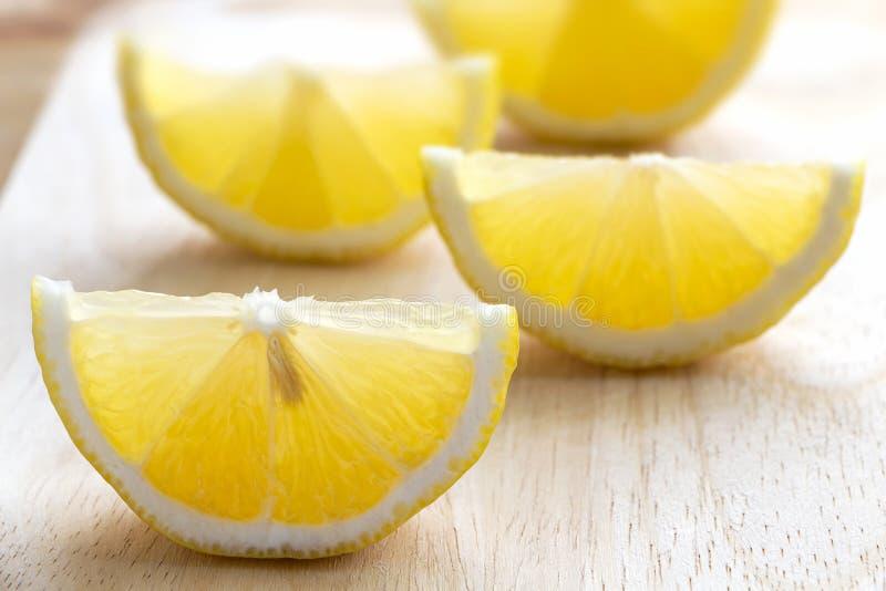 Verse die citroenen in stukken op een houten scherpe raad worden gesneden stock fotografie