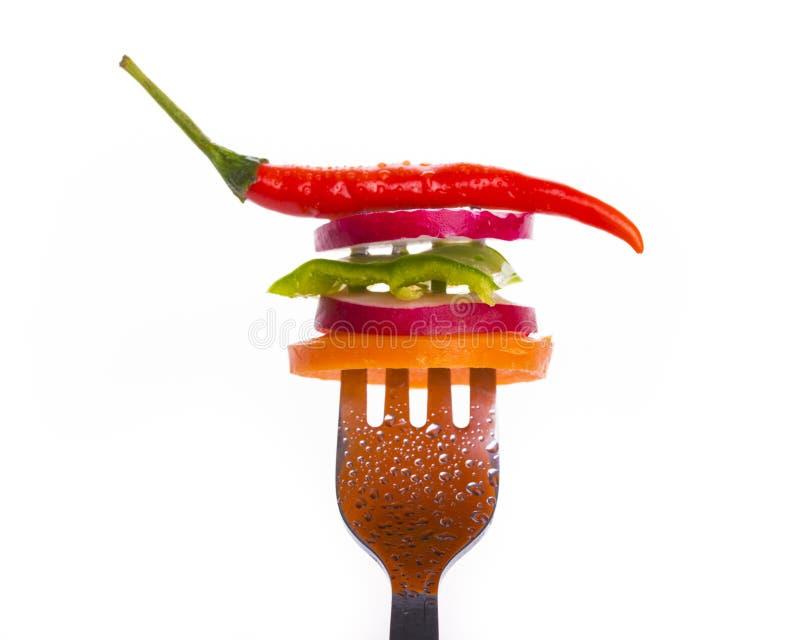 Verse die groenten op een vork op witte achtergrond wordt geïsoleerd royalty-vrije stock afbeeldingen