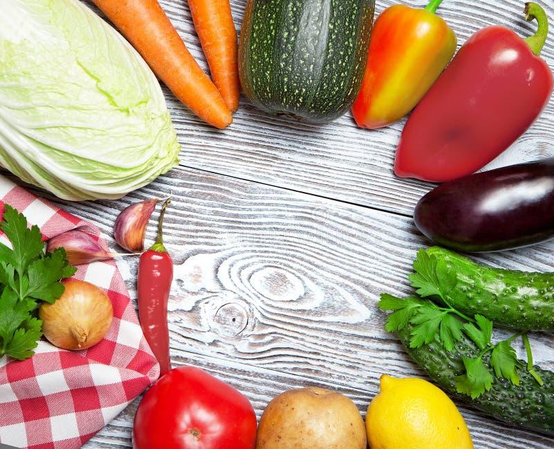 Verse die groenten rond op een witte houten lijst worden opgemaakt stock afbeeldingen