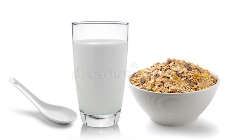 Verse die melk in het glas en muesliontbijt op witte bac wordt geplaatst stock foto