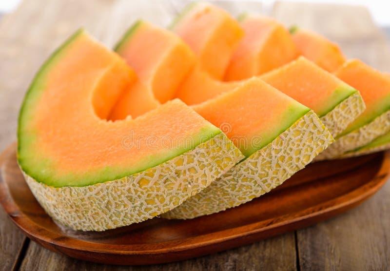 Verse die meloenen op houten plaat worden gesneden royalty-vrije stock afbeeldingen