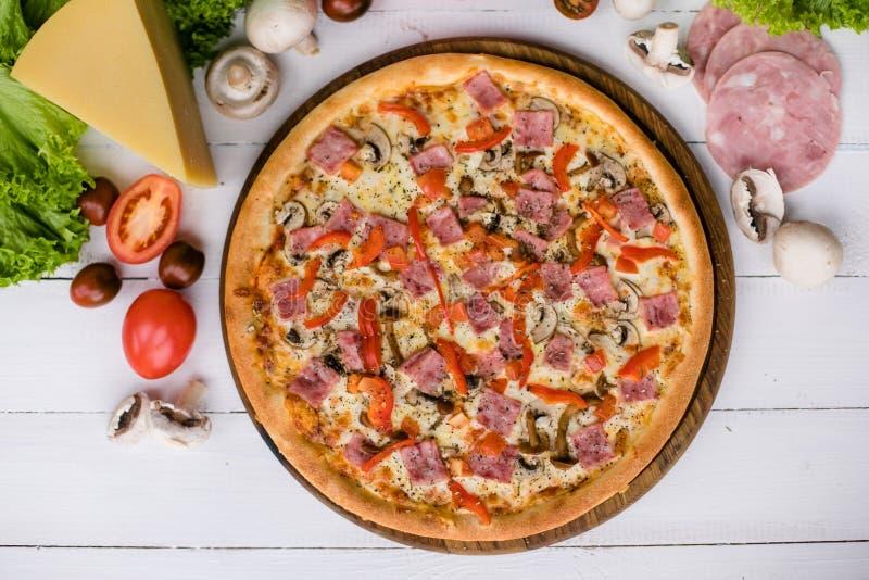 Verse die pizza door ingrediënten op lichte houten achtergrond wordt omringd royalty-vrije stock afbeeldingen