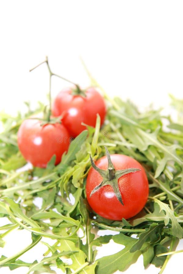 Verse die rucola met tomaten op wit worden geïsoleerd. stock afbeelding