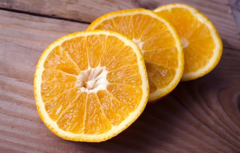 Verse die sinaasappelen op houten lijst worden gesneden Stilleven van rijp fruit Gesneden sappige citrusvruchten Oranje Achtergro royalty-vrije stock afbeelding