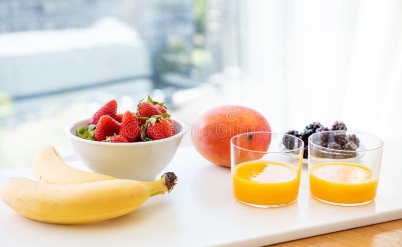 Verse die vruchten en jus d'orange op wit worden geïsoleerd Gezond Ontbijt voor twee stock afbeeldingen