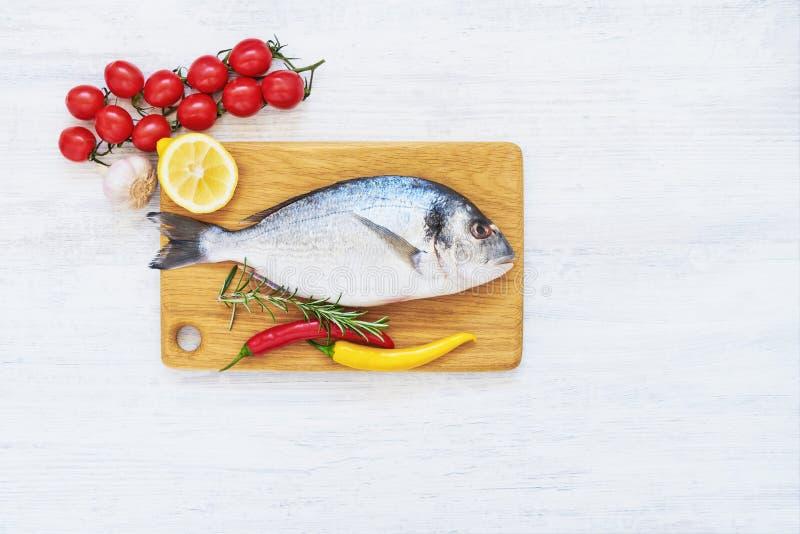 Verse doradavissen met kruiden op houten scherpe raad Gezond voedselconcept Hoogste mening, exemplaarruimte royalty-vrije stock fotografie