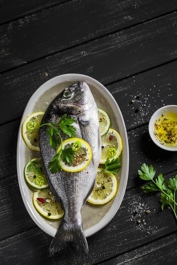 Verse Dorado-vissen met citroen, kalk en peterselie op een ovale schotel royalty-vrije stock afbeeldingen