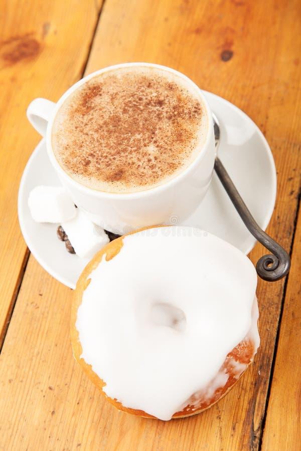 Verse doughnut en kop van cappuccino op houten lijst royalty-vrije stock afbeeldingen