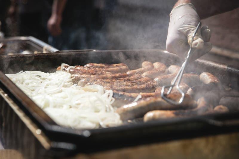 Verse Duitse worsten met uien bij de grill, braadworst stock foto's