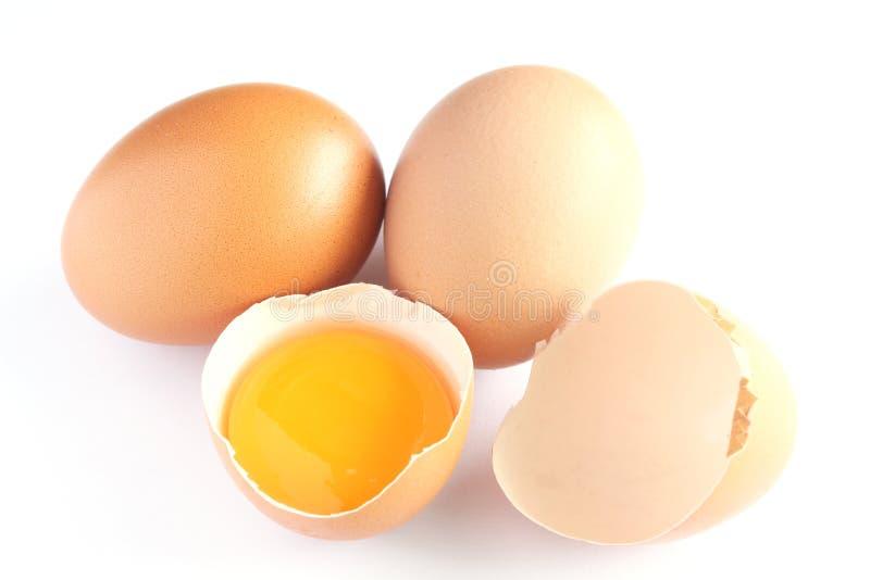 Verse eieren en dooier in shells op witte achtergrond stock foto's
