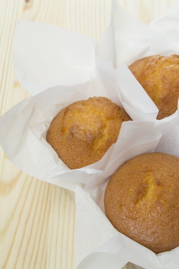 Verse eigengemaakte cupcakes in Witboek Het Cupcakesbaksel koekt zoete gouden verpakt in ambachtdocument Dessert 3 cupcakesclose- stock foto
