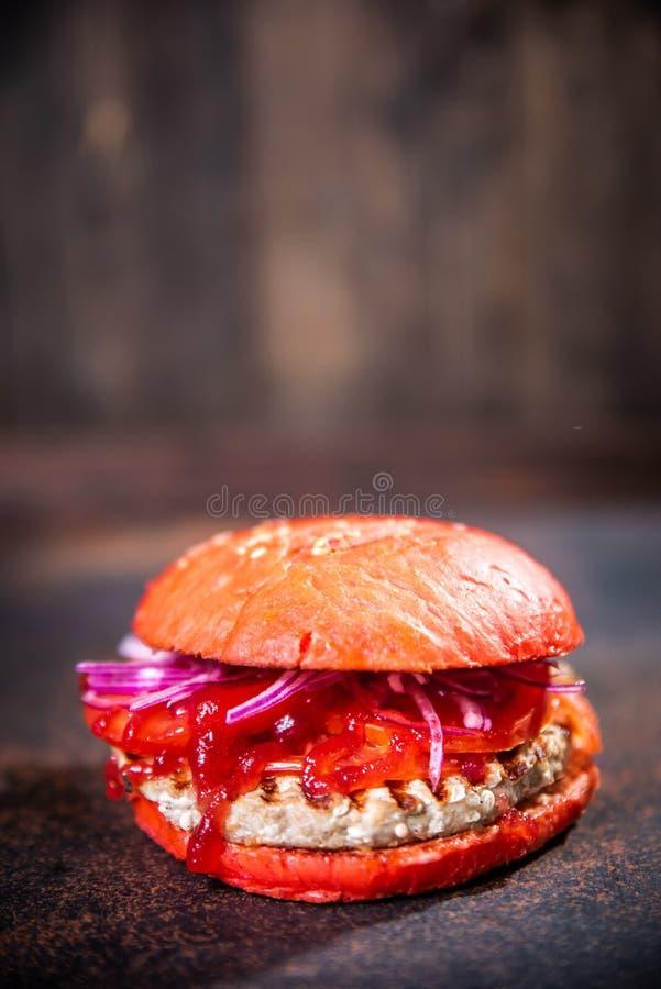 Verse eigengemaakte hamburger op houten raad over donkere houten achtergrond stock afbeelding