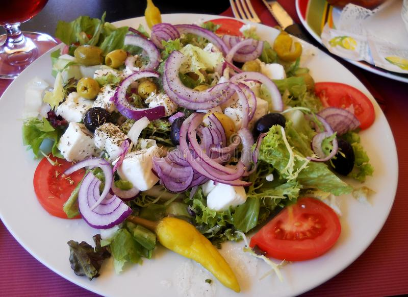 Verse en gezonde salade met rode ui, sla, tomaat, feta-kaas, olijven en peper stock afbeelding