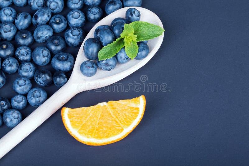 Verse en rijpe bosbessen in een houten lepel Een hoop van organische bessen en sappige citrusvrucht op een donkerblauwe achtergro stock afbeelding