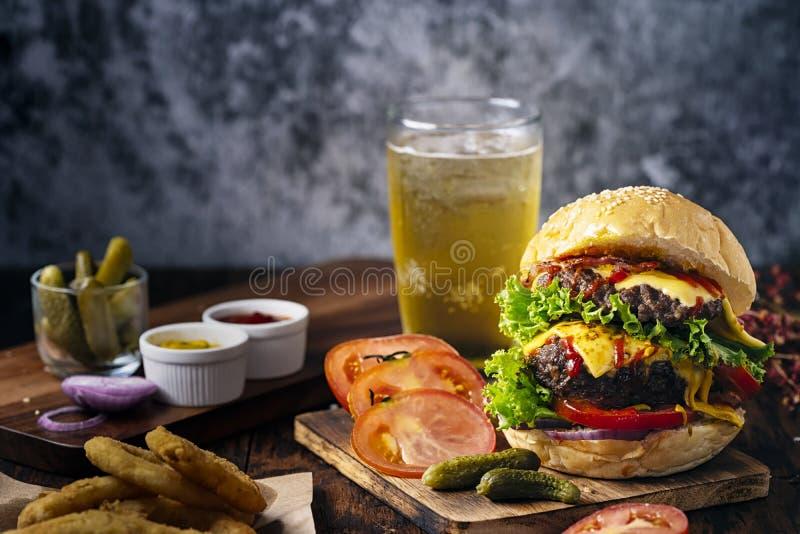 Verse en sappige hamburger Kaashamburger met rundvlees of bacon, pasteitjetomaat, uiring en sodawater of bier royalty-vrije stock afbeeldingen