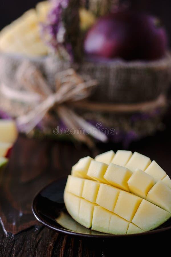 Verse en sappige mango, besnoeiing door de helften over houten lijst stock fotografie