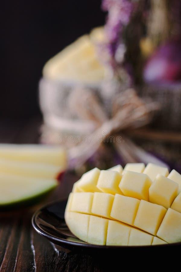 Verse en sappige mango, besnoeiing door de helften over houten lijst stock afbeeldingen