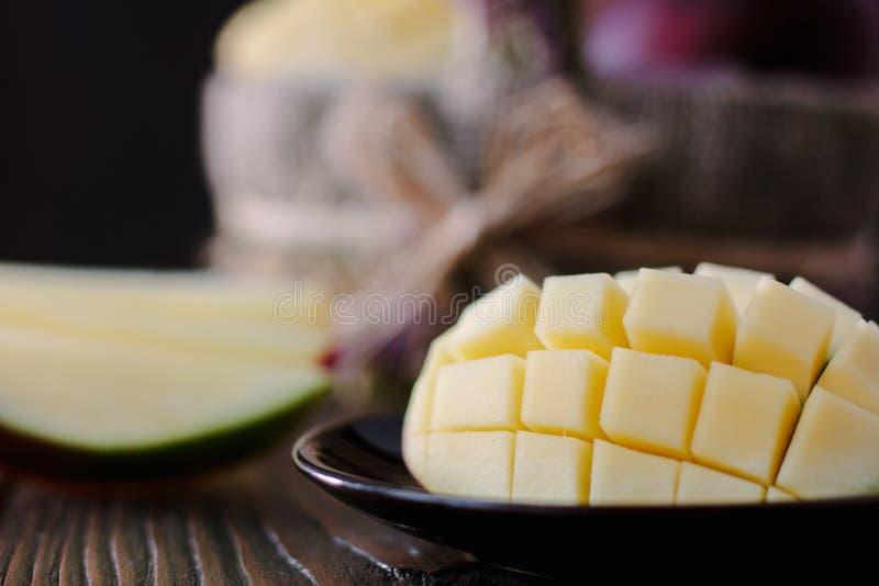 Verse en sappige mango, besnoeiing door de helften over houten lijst royalty-vrije stock foto's