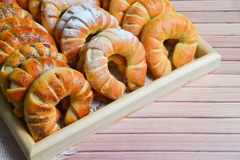 Verse enkel gebakken zoete broodjes of broodjes op dienblad voor ontbijt en thee of koffietijd op houten achtergrond royalty-vrije stock fotografie